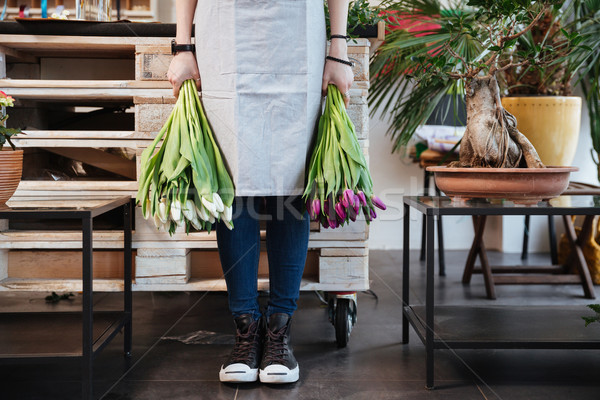 Woman florist standing and holding two bunches of tulips  Stock photo © deandrobot