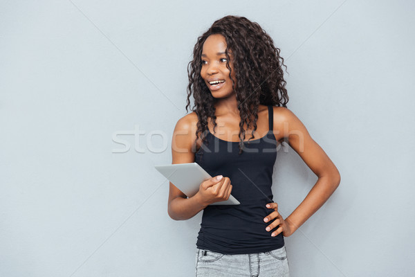Cheerful afro american woman holding tablet computer  Stock photo © deandrobot