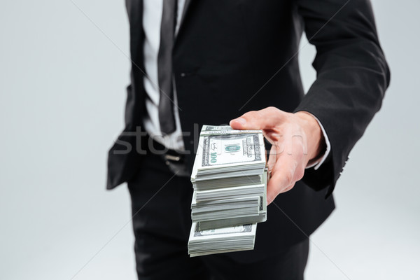 Businessman in suit and tie giving money to you Stock photo © deandrobot