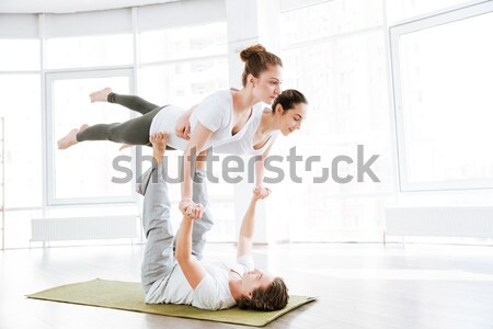 Couple doing flexibility workout in yoga studio Stock photo © deandrobot