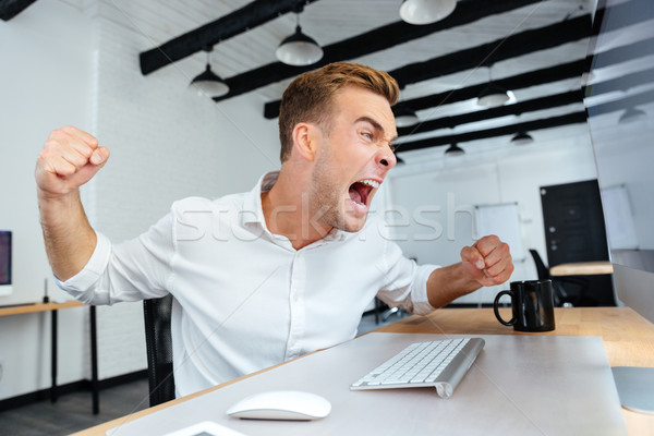 Mad aggressive young businessman shouting in office Stock photo © deandrobot