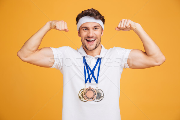 Cheerful young spotrsman with three medals showing biceps Stock photo © deandrobot