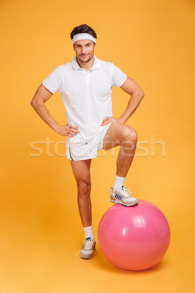 Young handsome sportsman with fitness ball holding hands on hips Stock photo © deandrobot