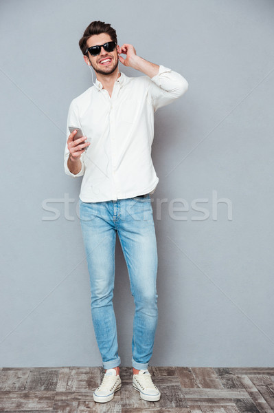 Cheerful man in sunglasses listening to music from cell phone Stock photo © deandrobot
