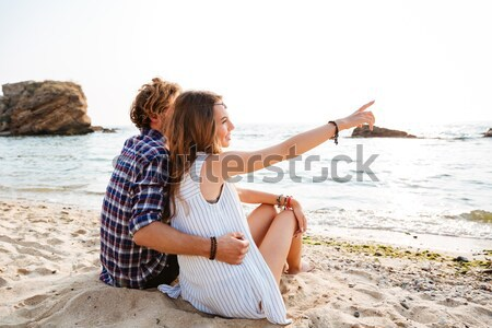 Man greating his girlfriend while sitting at the tent outdoors Stock photo © deandrobot
