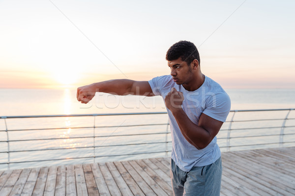 Handsome african man athlete boxing outdoors on sunrise Stock photo © deandrobot