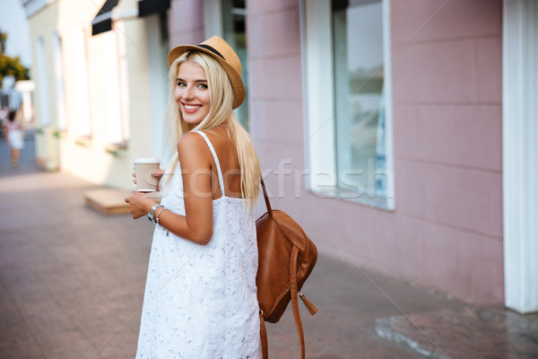 Back view of girl in dress holding take away cup Stock photo © deandrobot
