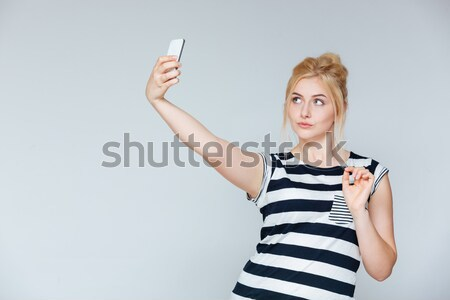 Smiling attractive young woman pointing away Stock photo © deandrobot
