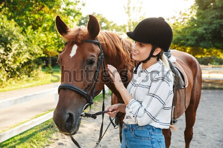 Happy woman cowgirl taking care of her horse on ranch Stock photo © deandrobot