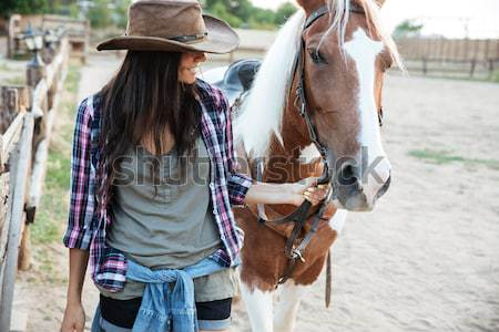 Cheerful woman cowgirl playing with horse in countryside Stock photo © deandrobot