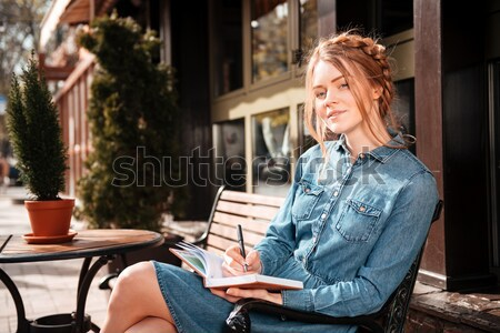 Thoughtful woman sitting and reading a book in outdoor cafe Stock photo © deandrobot