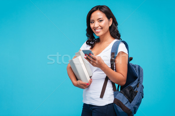 Cheerful young vietnamese girl holding backpack and books using smartphone Stock photo © deandrobot