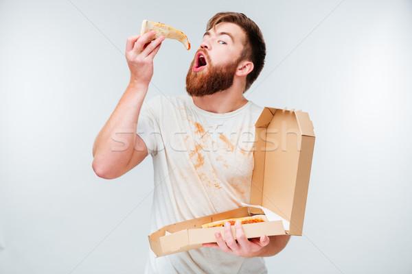 Grappig bebaarde hongerig man eten pizza Stockfoto © deandrobot