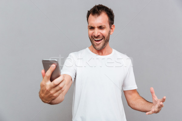 Angry casual man holding smartphone Stock photo © deandrobot