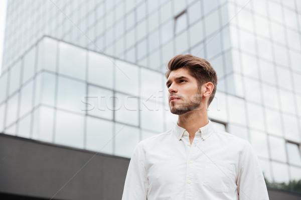 Handsome young businessman standing near business center Stock photo © deandrobot
