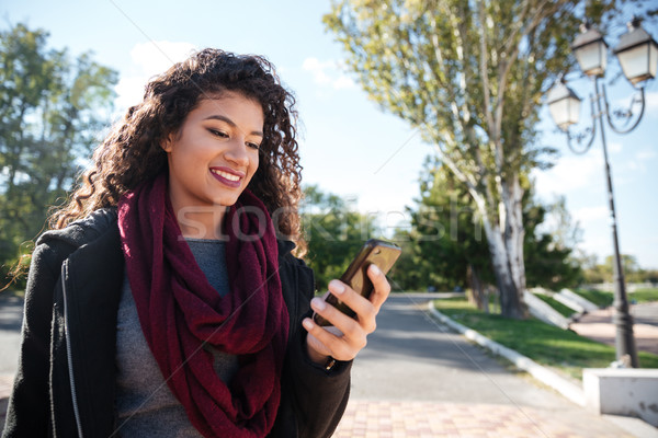 Incredible dark-skinned young woman chatting Stock photo © deandrobot