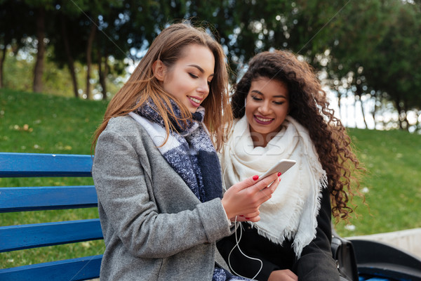Incredible young ladies sitting on bench and listening music together Stock photo © deandrobot