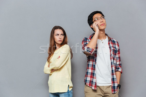 Upset angry girl watching her boyfriend talking on mobile phone Stock photo © deandrobot