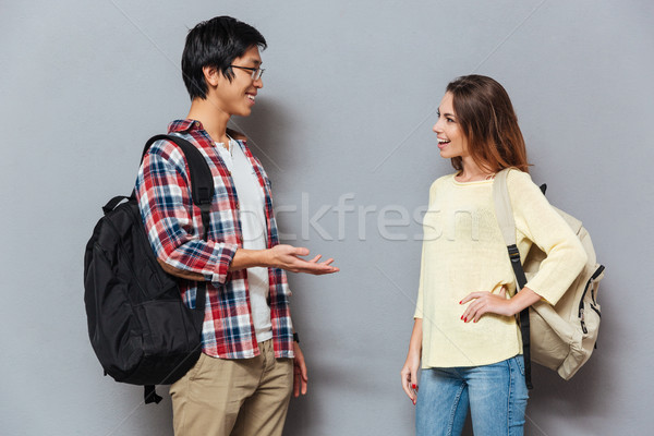 Two young interracial students with backpacks talking Stock photo © deandrobot