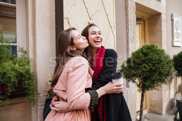 Sisters in coats are cuddling Stock photo © deandrobot