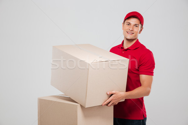 Courier in red cap holding box and looking at camera Stock photo © deandrobot