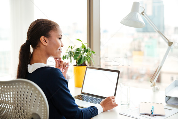 Back view of african business woman using laptop in office Stock photo © deandrobot