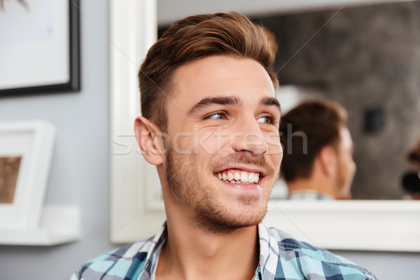 Cheerful young man sitting on sofa in home Stock photo © deandrobot