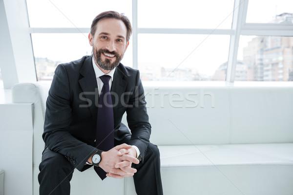 Elderly bearded business man sitting on sofa near the window Stock photo © deandrobot