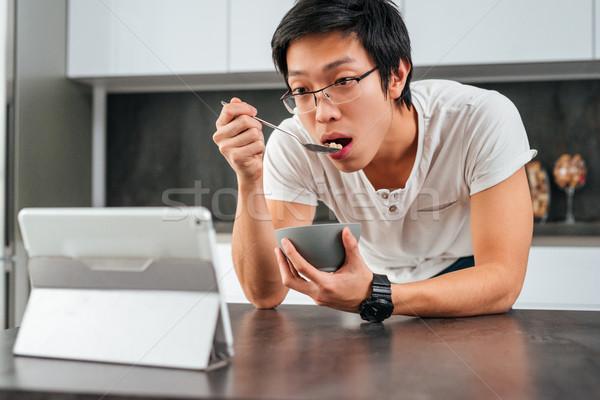 Asian man eating cereal Stock photo © deandrobot
