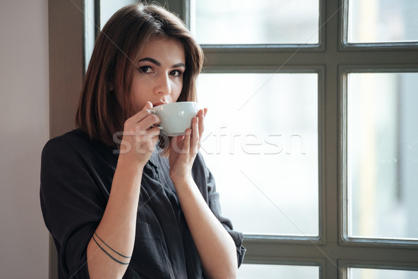 Young incredible cheerful woman drinking coffee. Stock photo © deandrobot