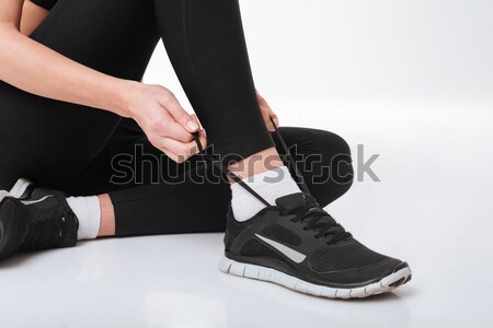 Closeup of sportswoman sitting and tying shoelaces Stock photo © deandrobot