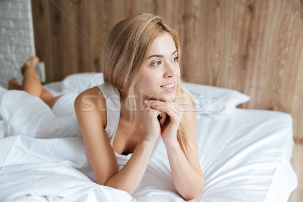Stock photo: Pensive woman lying and thinking on bed in bedroom