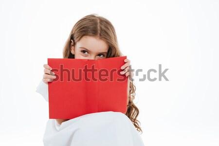 Cute playful little girl hiding behind red book Stock photo © deandrobot