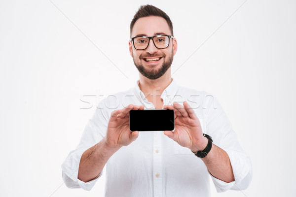 Smiling young bearded man showing phone display to camera Stock photo © deandrobot