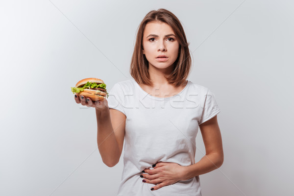 Confused young woman holding fastfood and touching belly Stock photo © deandrobot
