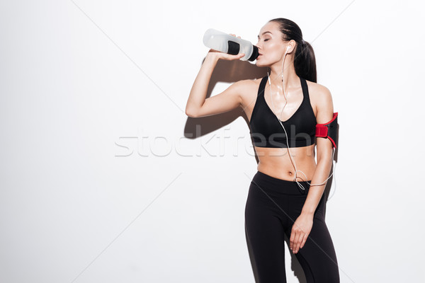 Attractive woman with armband drinking water and listening to music Stock photo © deandrobot