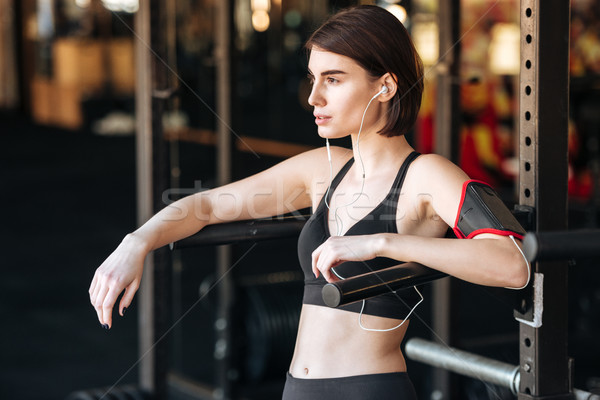 Sportswoman doing exercises and listening to music in gym Stock photo © deandrobot