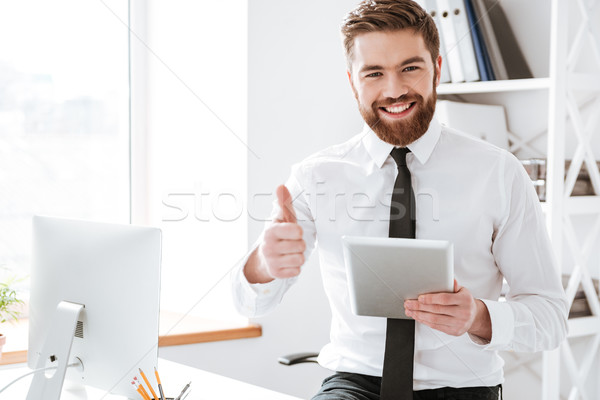 Businessman holding tablet and make thumbs up gesture. Stock photo © deandrobot