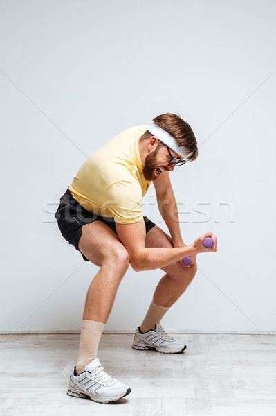 Vertical image of male nerd training with light dumbbells Stock photo © deandrobot