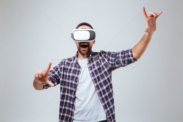 Happy Bearded man in shirt using virtual reality device Stock photo © deandrobot