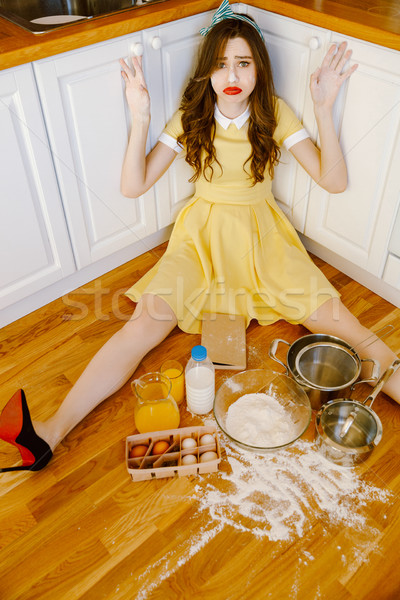 Confused pin-up woman sitting on floor at kitchen and cooking. Stock photo © deandrobot