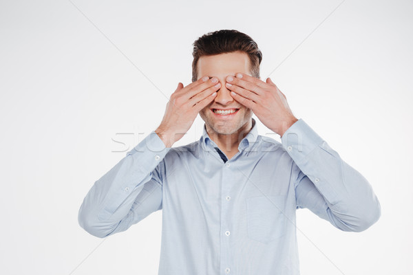 Smiling business man covering eyes of both hands Stock photo © deandrobot