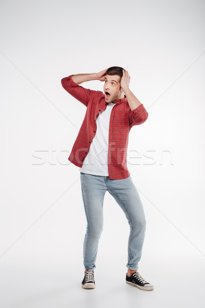 Vertical image of shocked man holding head Stock photo © deandrobot