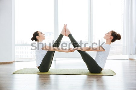 Two women balancing and practicing yoga in studio Stock photo © deandrobot