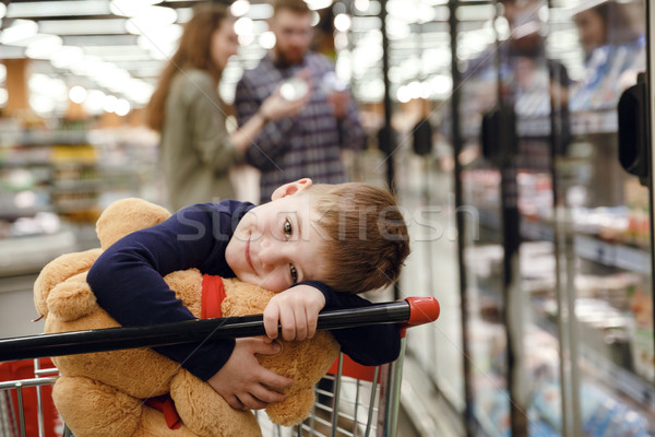 Smiling boy sitting in shopping trolley Stock photo © deandrobot