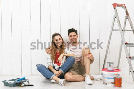 Happy multiethnic young couple renovating home and using mobile phone Stock photo © deandrobot