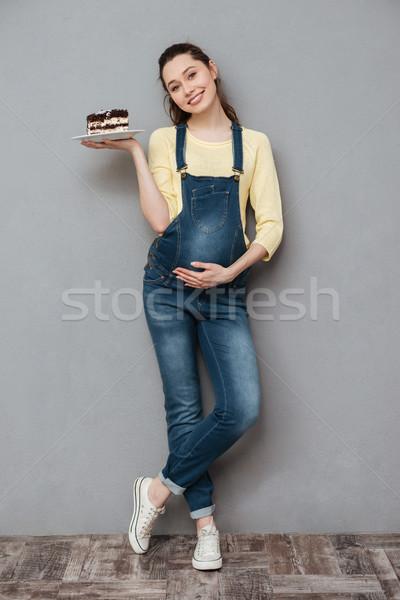 Happy pregnant lady holding sweet cake. Stock photo © deandrobot