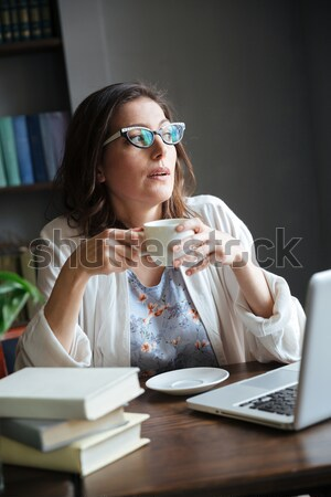Beautiful woman writer sitting indoors while talking by phone Stock photo © deandrobot