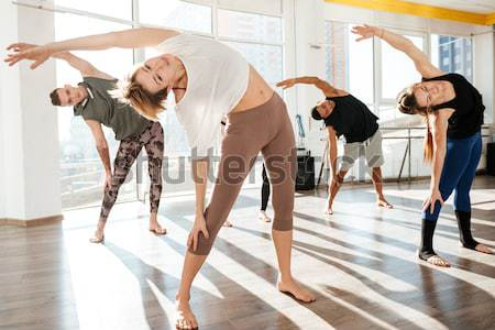 Image of young people doing yoga in gym Stock photo © deandrobot
