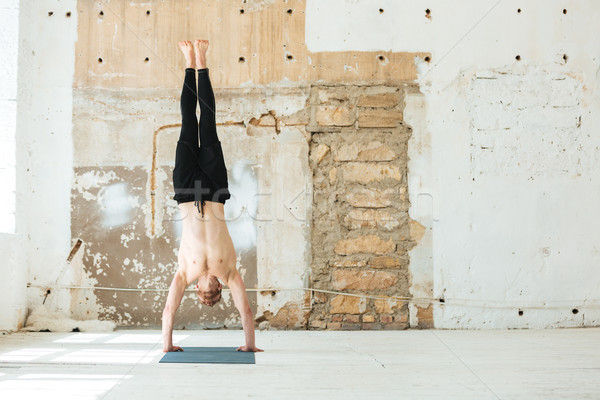 Full length of a man practising yoga poses Stock photo © deandrobot